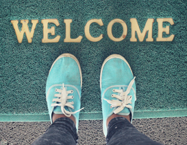 Arial view of feet standing on a doormat that says Welcome